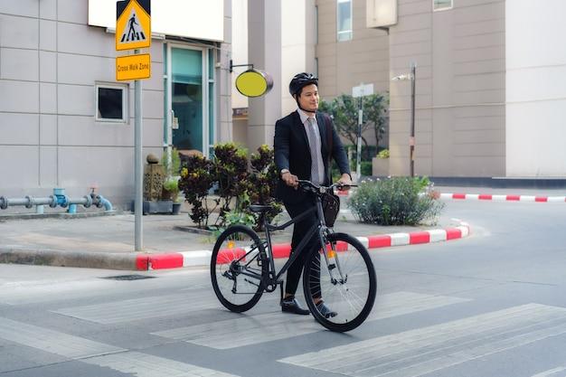 L'uomo d'affari asiatico spinge una bicicletta attraverso un attraversamento pedonale