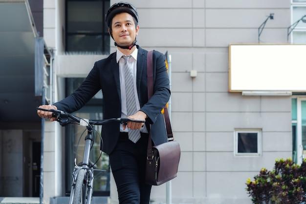 Uomo d'affari asiatico che spinge la sua bicicletta da casa la mattina