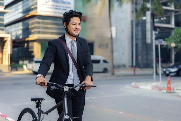Uomo d'affari asiatico che spinge la sua bicicletta da casa