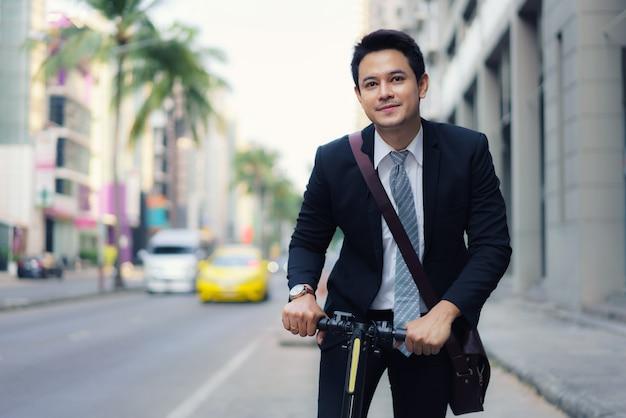 Uomo d'affari asiatico che guida uno scooter elettrico per le strade della città per andare a lavorare la mattina