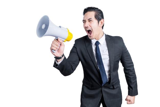 Uomo d'affari asiatico gridare sul megafono isolato sopra la parete bianca