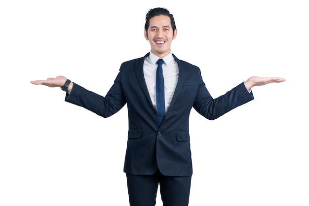 Uomo d'affari asiatico che mostra la mano vuota isolata sopra la parete bianca