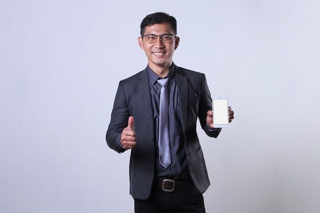 Uomo d'affari asiatico che mostra uno smartphone e fa i pollici in su