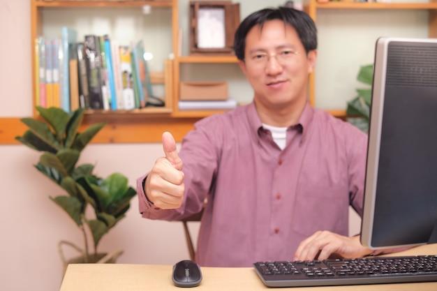 Uomo d'affari asiatico che mostra i pollici in su mentre si utilizza il computer, seduto in ufficio a casa, soluzioni efficaci, raccomandando la scelta migliore per le imprese