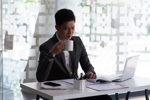Uomo d'affari asiatico seduto in ufficio a bere caffè e controllare documenti laptop sul tavolo.