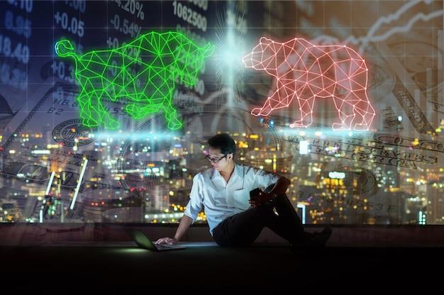 Uomo d'affari asiatico seduto e usando il telefono cellulare intelligente che mostra il toro e l'orso poligonali