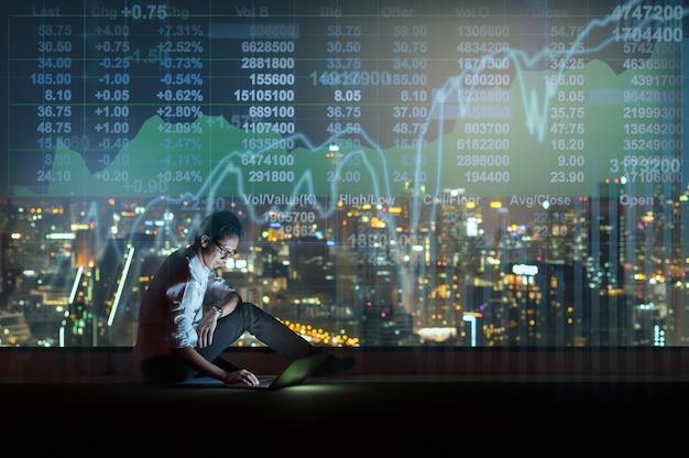 Uomo d'affari asiatico seduto e usando il telefono cellulare intelligente che mostra il mercato azionario