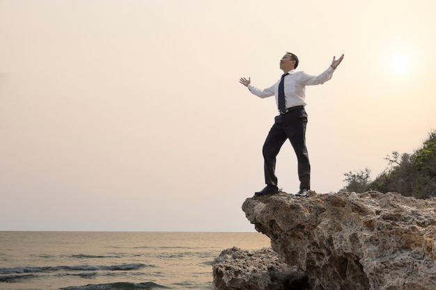 Uomo d'affari asiatico in piedi sulla scogliera con due braccia che si alzano mostrando grande piacere o felice soddisfazione del divertimento quando l'obiettivo aziendale viene raggiunto o il duro lavoro è finito