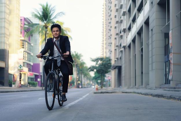L'uomo d'affari asiatico in un vestito sta andando in bicicletta per le strade della città per il suo tragitto mattutino al lavoro. concetto di trasporto eco.