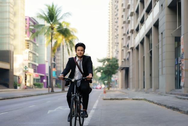 L'uomo d'affari asiatico in un vestito sta andando in bicicletta per le strade della città per il suo tragitto mattutino al lavoro