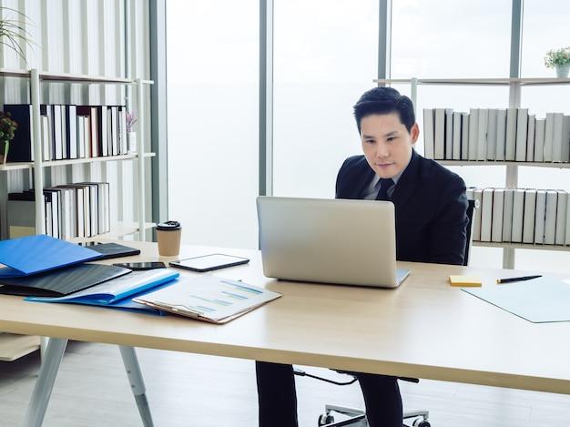 Uomo d'affari asiatico in vestito che si siede al tavolo e lavora al computer portatile in ufficio