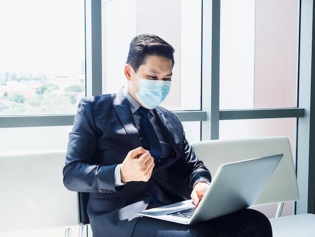 L'uomo d'affari asiatico in vestito che indossa la maschera protettiva ha alzato la mano felice e allegro quando ha visto un monitor portatile sulle sue ginocchia