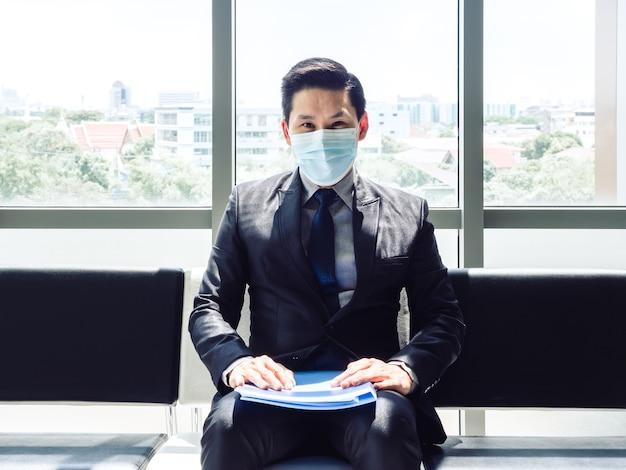 Uomo d'affari asiatico in vestito che indossa la maschera protettiva che si siede e che guarda l'obbiettivo e in attesa di un colloquio di lavoro vicino all'enorme finestra di vetro in un edificio moderno