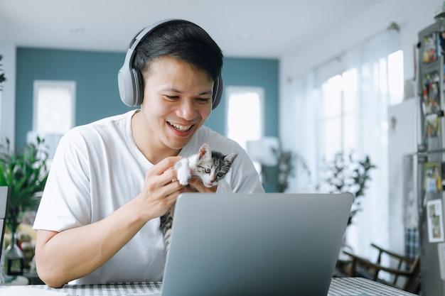 Uomo d'affari asiatico che parla con il team di colleghi in videoconferenza con gattino e faccia sorridente. uomo che utilizza computer portatile e cuffie per riunioni online. smart working dal concetto di casa.