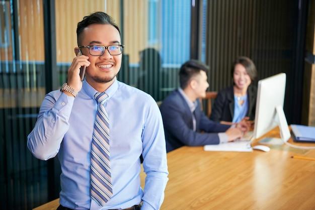 Uomo d'affari asiatico che comunica sul telefono