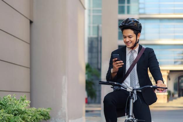 Uomo d'affari asiatico che utilizza i loro telefoni cellulari per visualizzare applicazioni, mappe, indicazioni per lavorare al mattino.
