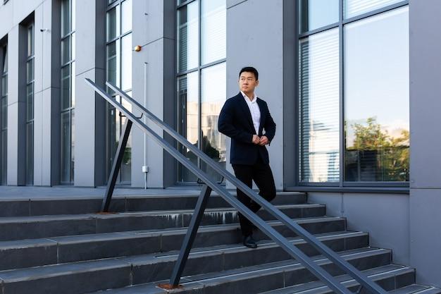 L'uomo d'affari asiatico sale le scale del centro uffici, l'uomo si precipita a un incontro di lavoro in giacca e cravatta