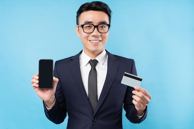 Uomo d'affari asiatico che indossa tuta in possesso di smartphone e carta di credito