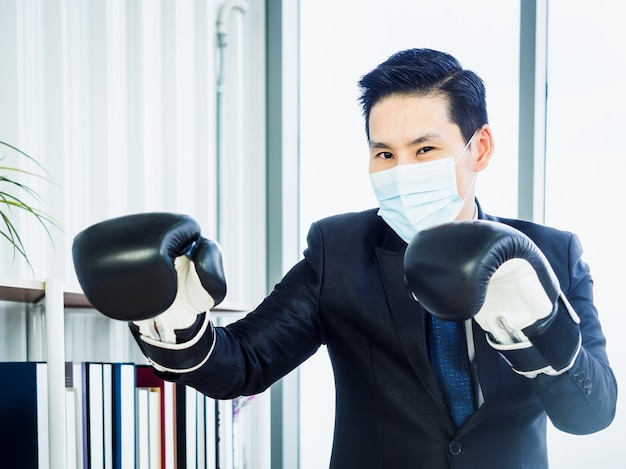 Uomo d'affari asiatico che indossa tuta e maschera protettiva e guantoni da boxe da portare mano in ufficio