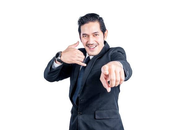 Uomo d'affari asiatico con un'espressione di chiamarmi isolato sopra il muro bianco