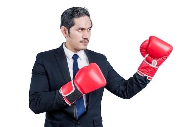 Uomo d'affari asiatico con guantoni da boxe rossi combattimenti isolati su muro bianco
