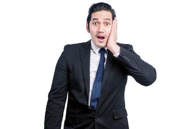 Uomo d'affari asiatico con un'espressione scioccata isolata sopra il muro bianco