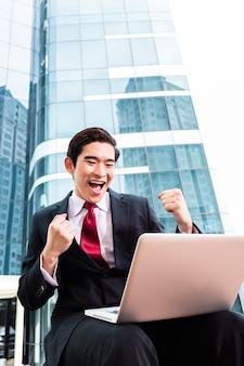 Uomo d'affari asiatico che lavora al computer portatile davanti all'edificio a torre