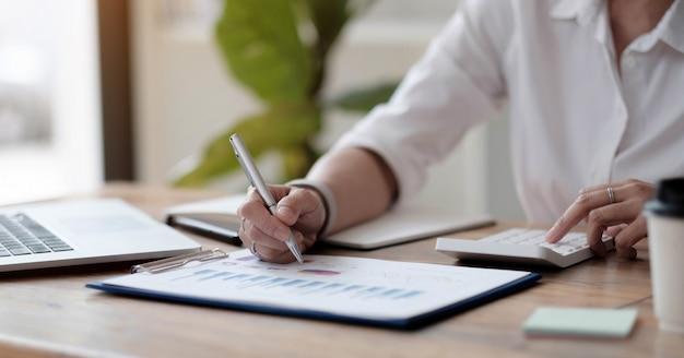 Donna d'affari asiatica o ragioniere che lavora puntando grafico discussione e analisi dati grafici e grafici e utilizzando una calcolatrice per calcolare i numeri.finanze aziendali e concetto di contabilità
