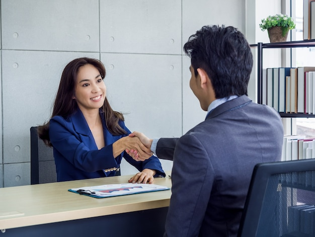 Asian imprenditrice e imprenditore indossando tuta stringe la mano in ufficio