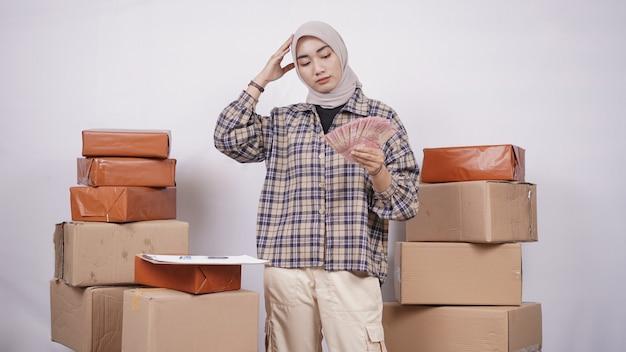 Donna d'affari asiatica confusa con la quantità di denaro isolata su sfondo bianco