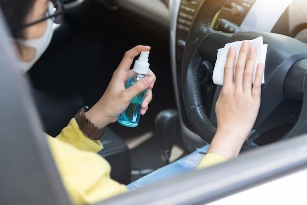 La donna di affari asiatica in camicia verde con la maschera protettiva usando lo spruzzo dell'alcool del disinfettante e la strofinata del tessuto bagnato sul volante prevengono l'epidemia di coronavirus o coronavirus nella sua automobile.