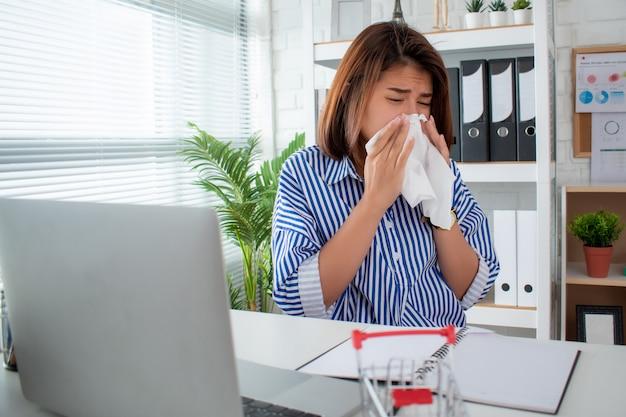 Una donna d'affari asiatica starnutisce e tossisce sulla sua scrivania in ufficio.