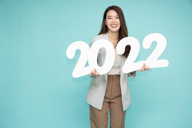 Donna d'affari asiatica che tiene i numeri 2022 isolati su sfondo verde