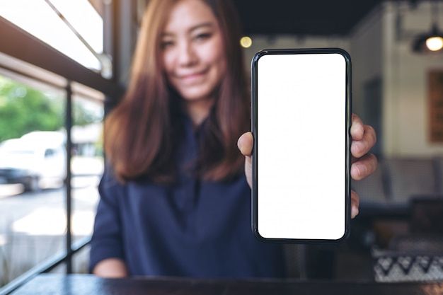 Una donna d'affari asiatica in possesso e mostrando il telefono cellulare nero con schermo bianco vuoto nella caffetteria