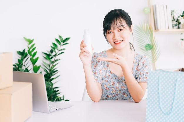 La donna d'affari asiatica utilizza gli smartphone per trasmettere in streaming la vendita di cosmetici sui siti di social networking e sui siti di e-commerce.