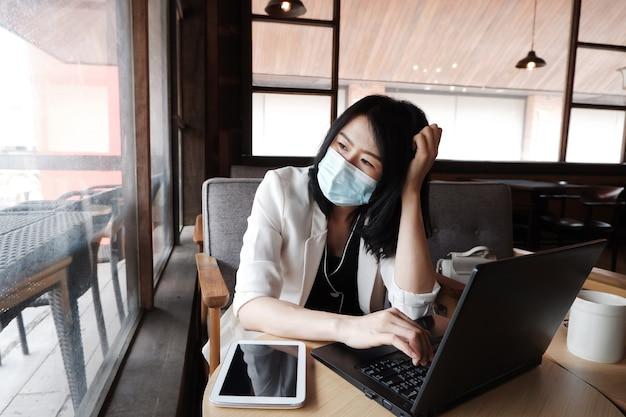 La donna di affari asiatica indossa la maschera per prevenire civid-19 e lavora online con il laptop in ufficio.