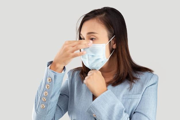 Donna di affari asiatica in una mascherina medica isolata su un grigio