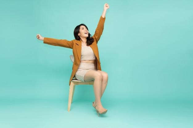 Donna d'affari asiatica seduta su una sedia e con le mani in alto le braccia alzate dalla felicità