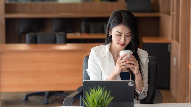 Donna d'affari asiatica seduta e bere caffè con tablet in ufficio.