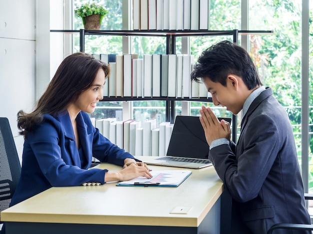 Donna di affari asiatica in vestito che guarda uomo d'affari che saluto con le mani per pagare rispetto stile tailandese in ufficio