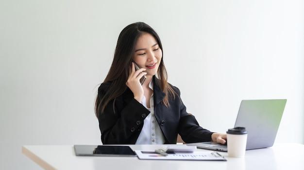 Imprenditrice asiatica parlando al telefono utilizzando laptop e grafico alla scrivania dell'ufficio.