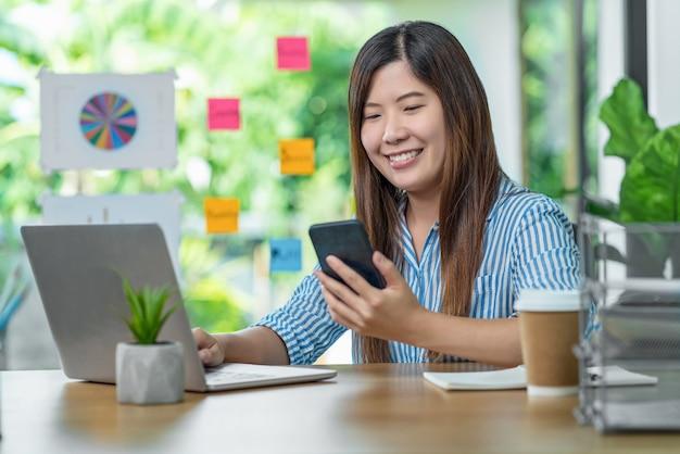 Donna d'affari asiatica che utilizza il telefono cellulare e lavora con il computer portatile nel soggiorno interno