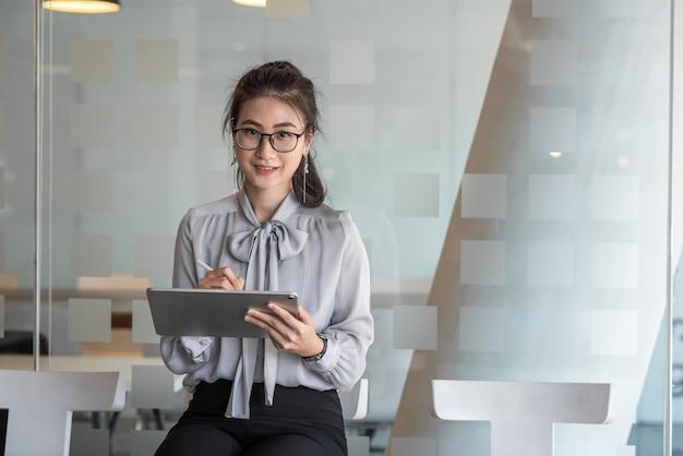 Donna di affari asiatica in attesa di un colloquio di lavoro felice in ufficio con un tablet.