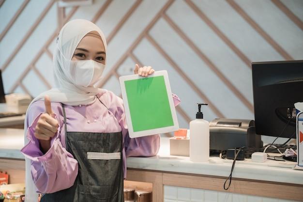Sciarpa e maschera di usura asiatica della donna di affari che stanno al suo deposito che mostra il pc in bianco della compressa alla macchina fotografica