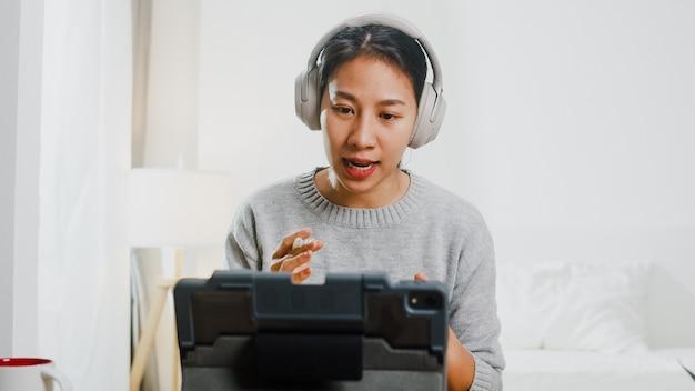 Imprenditrice asiatica indossare le cuffie utilizzando tablet parlare con i colleghi del piano in videochiamata mentre si lavora da casa in camera da letto