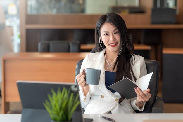 Donna d'affari asiatica che indossa le cuffie e tiene in mano una tazza di caffè e un libro seduto rilassa il tablet è posizionato al tavolo dell'ufficio. guardando la fotocamera.