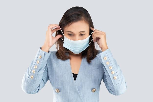 Imprenditrice asiatica che indossa una maschera medica isolata su uno sfondo grigio.