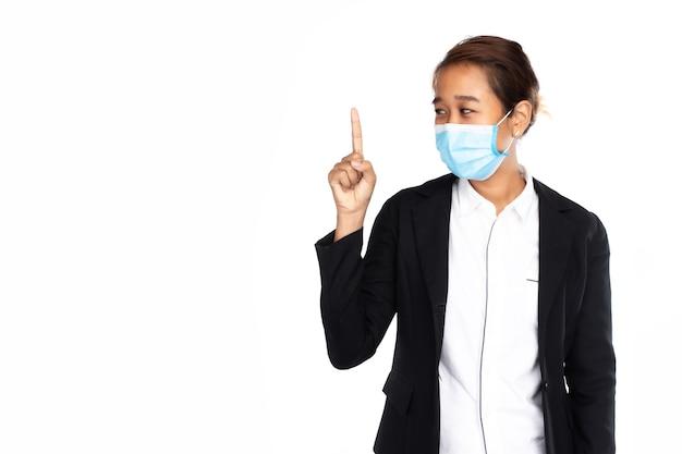 Donna di affari asiatica che indossa la maschera chirurgica in giacca formale nera, dito puntato
