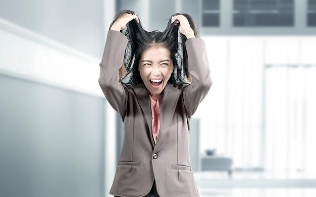 Donna di affari asiatica con l'espressione sollecitata sulla stanza dell'ufficio