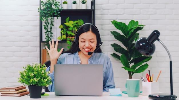 Donna di affari asiatica che lavora da casa con il computer portatile